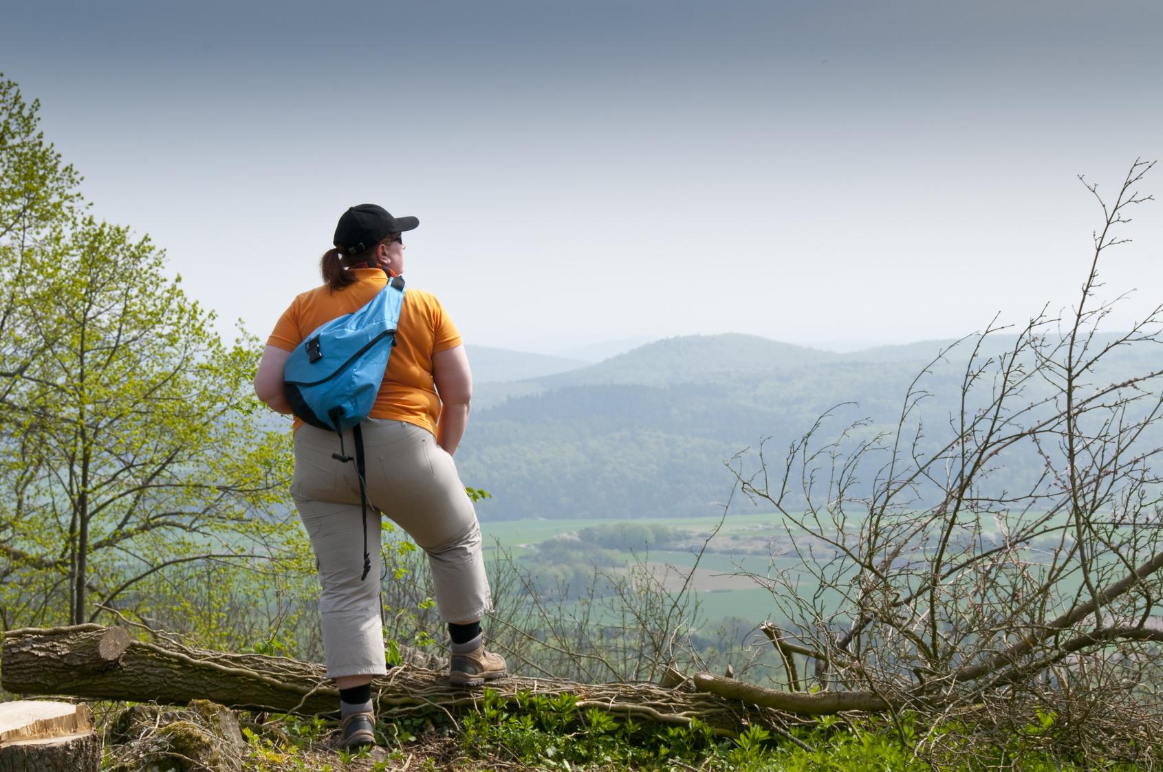 Übergewichtige Wanderin schaut in die Landschaft, Rückansicht